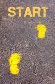 Yellow footsteps on sidewalk towards Start message — Stock Photo