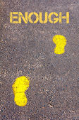 Yellow footsteps on sidewalk towards Enough message — Stock Photo