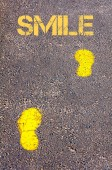 Yellow footsteps on sidewalk towards Smile message — Stock Photo