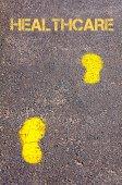 Gul fotspår på trottoaren mot hälso-och meddelande — Stockfoto