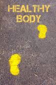 Yellow footsteps on sidewalk towards Healthy Body message — ストック写真
