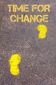 Yellow footsteps on sidewalk towards Time for Change message — Stock Photo