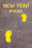 Yellow footsteps on sidewalk towards New Year Ahead message — Stock Photo