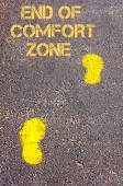 Yellow footsteps on sidewalk towards End of Comfort Zone message — Stock Photo