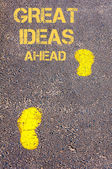 Yellow footsteps on sidewalk towards Great Ideas Ahead message — Φωτογραφία Αρχείου