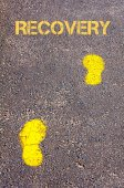 Yellow footsteps on sidewalk towards Recovery message — Stock Photo