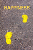 Yellow footsteps on sidewalk towards Happiness message — Stock Photo