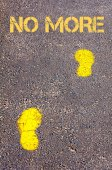 Yellow footsteps on sidewalk towards No More message — Stock Photo