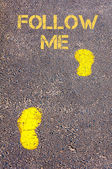 Yellow footsteps on sidewalk towards Follow Me message — Stock Photo