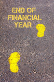 Yellow footsteps on sidewalk towards End of Financial Year message — Stock Photo