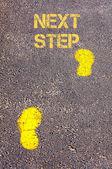 Żółte ślady na chodniku w kierunku następnego kroku wiadomość — Zdjęcie stockowe