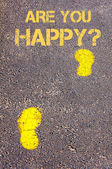 Yellow footsteps on sidewalk towards Are You Happy message — Stock Photo