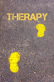 Yellow footsteps on sidewalk towards Therapy message — Stock Photo
