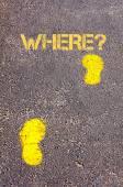 Yellow footsteps on sidewalk towards Where message — Stockfoto