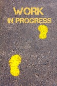 Yellow footsteps on sidewalk towards Work in Progress message — Stock Photo