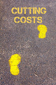 Yellow footsteps on sidewalk towards Cutting costs message — Stock Photo