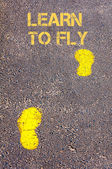 Yellow footsteps on sidewalk towards Learn to fly message — Stock Photo