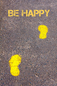 Yellow footsteps on sidewalk towards Be Happy message — Stock Photo