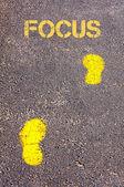 Yellow footsteps on sidewalk towards Focus message — Stock Photo