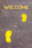 Yellow footsteps on sidewalk towards Welcome message — Stock Photo