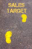 Yellow footsteps on sidewalk towards Sales Target message — Stock Photo