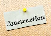Recycled paper note pinned on cork board. Construction Message — Foto de Stock
