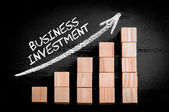 Words Business Investment on ascending arrow above bar graph — ストック写真