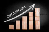 Word Expectations on ascending arrow above bar graph — Стоковое фото