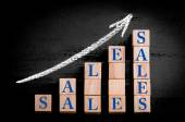 Word SALES on ascending arrow above bar graph — Stock Photo