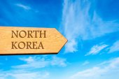 Wooden arrow sign pointing destination NORTH KOREA — Stock Photo