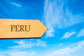 Wooden arrow sign pointing destination PERU — Stock Photo