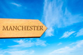 Wooden arrow sign pointing destination MANCHESTER, ENGLAND — Stock Photo
