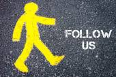 Yellow pedestrian figure walking towards FOLLOW US — Stock Photo
