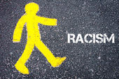 Yellow pedestrian figure walking towards RACISM — Stock Photo