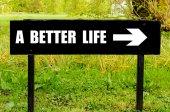 Лучшей жизни, написанные на направленный черный металлический знак — Стоковое фото