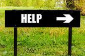 Pomoc na kierunkowe czarny metalowy znak — Zdjęcie stockowe