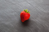 Red strawberry on slate background with copy space. — Stock Photo