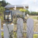 Kerosene lantern standing on the fence. house in the background — Stock Photo #70404867