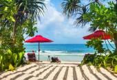 Beach vacation. Photo of sun loungers under the red sun umbrella — Stock Photo