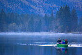 Family boattrip on hintersee on a foggy morning — Stock Photo