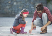 Mother and daughter are painting on the street. — Stock Photo