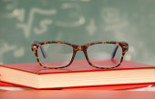 Glasses laying on a staple of Books — Stock fotografie