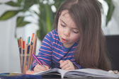 Child is Painting on a coloring book — Stock Photo