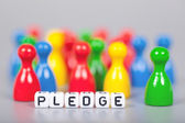Cube Letters show pledge  in front of unsharp ludo figures — Stock Photo