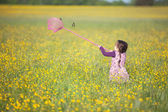 Little girl trying to catch a butterfly with a net — Stock Photo
