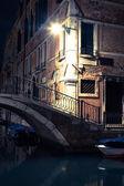 Venice canal late at night with street light illuminating bridge — Stock Photo