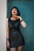 Pretty goth girl posing against a blue wall — Stok fotoğraf