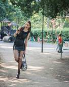 Pretty goth girl using phone in a city park — Стоковое фото