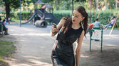 Pretty goth girl using phone in a city park — Stock Photo