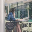 Pretty girl sitting in restaurant framed through the glass of a window — Stock Photo #55906097